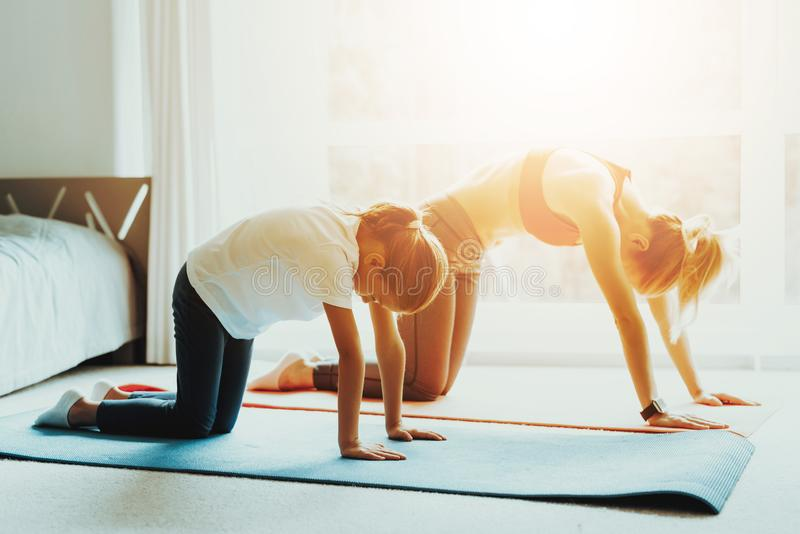 Mum And Daughter Back Stretching. Yoga Training. Active Lifestyle. Relaxing Together. Doing Fitness At Home. Holiday Leisure. Body Balance. Sport Exercise royalty free stock images