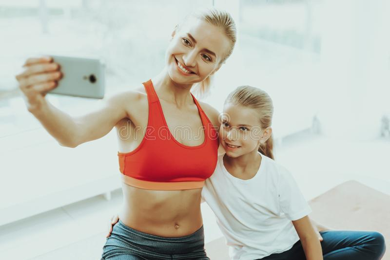 Mum And Daughter Are Doing Selfie On Gym Carpet. Mum And Daughter Are Doing Selfie On A Gym Carpet. Lotus Position. Relaxing Together. Fitness At Home. Holiday stock photography