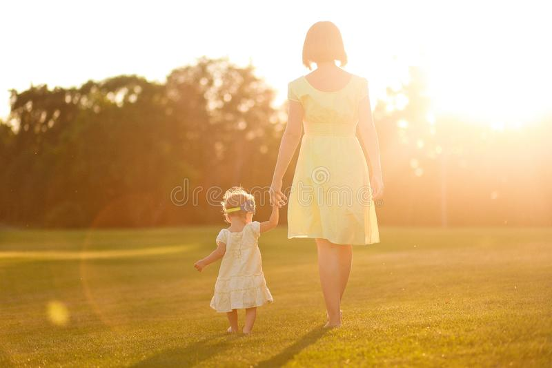 Mum daughter dresses barefooted legs hands grass sunset. Mum and daughter in dresses and with barefooted legs leave keeping for hands on grass on the sunset royalty free stock images