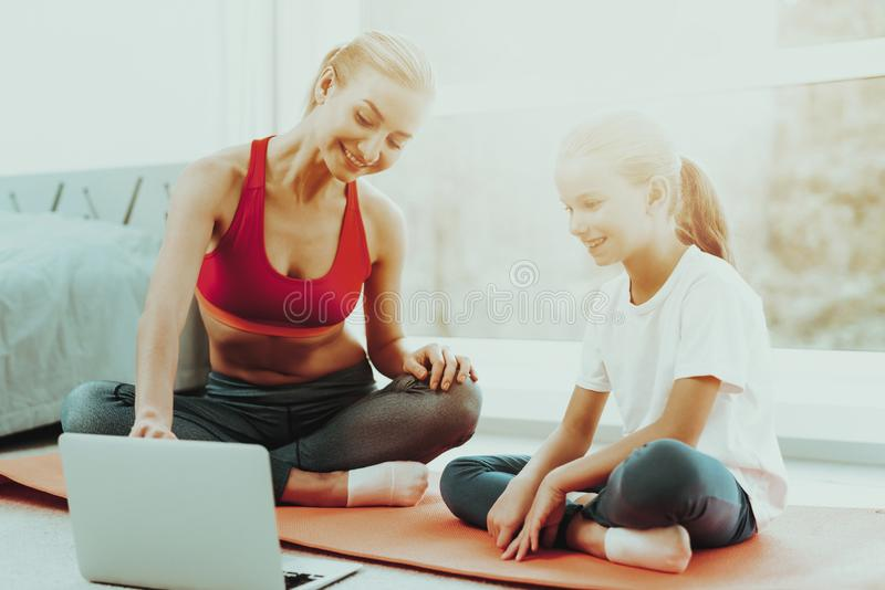 Mum And Daughter Stare On Laptop. Lotus Pose. Smiling Mum And Daughter Are Staring On A Laptop Screen. Lotus Position Concept. Yoga Meditation. Relaxing stock photos