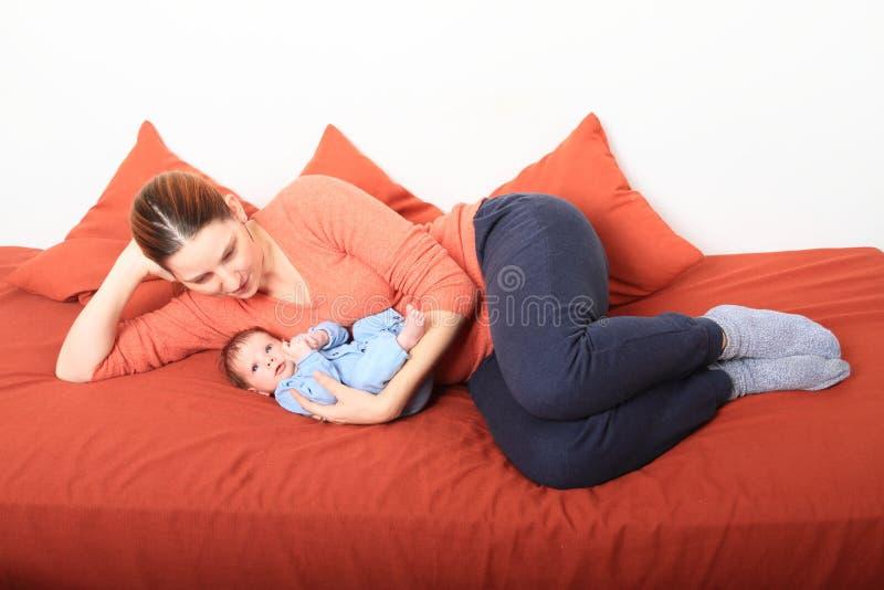 Mum de sorriso com o bebê recém-nascido surpreendido imagem de stock