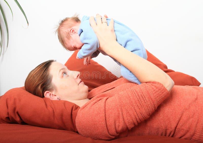 Mum de sorriso que guarda o bebê recém-nascido de grito fotografia de stock royalty free