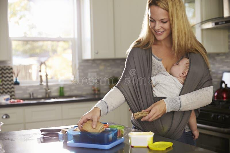 Mum die lunchbox voorbereiden terwijl babyslaap op haar in een drager royalty-vrije stock afbeeldingen