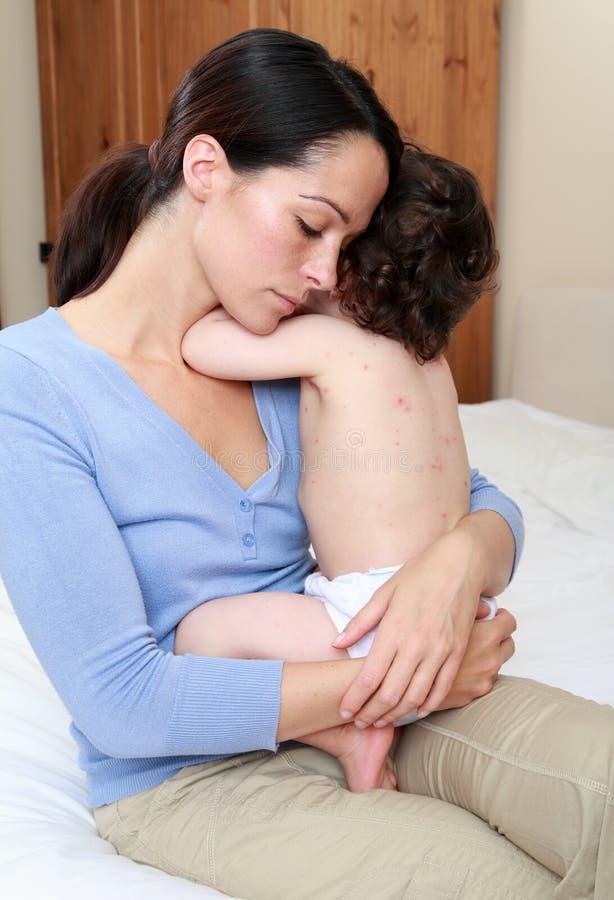 Mum die zieke baby troost stock fotografie