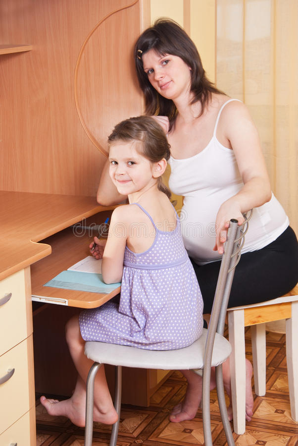 Mum does homework with a daughter royalty free stock photo