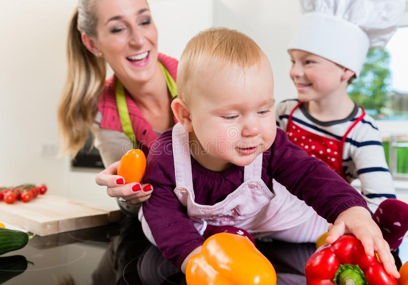 Mum e duas crianças que cozinham junto na cozinha fotografia de stock