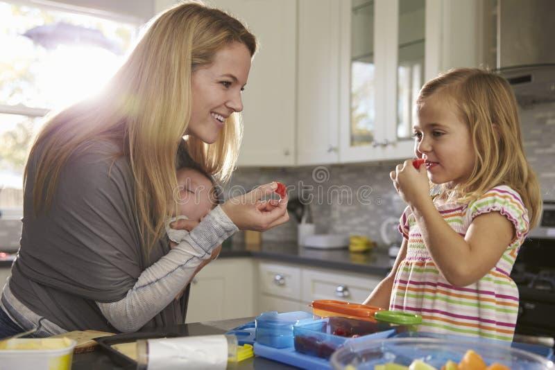 Mum e filha mais idosa que comem o fruto, quando o bebê dormir no portador de bebê imagem de stock royalty free