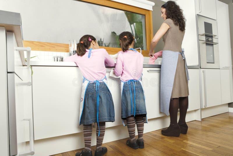 Mum e filhas que lavam acima na cozinha fotografia de stock royalty free