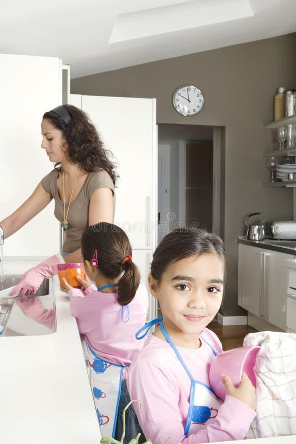 Mum en Dochters die omhoog in Keuken wassen stock afbeeldingen