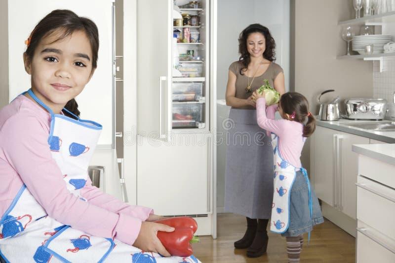 Mum en Dochters in Keuken stock foto