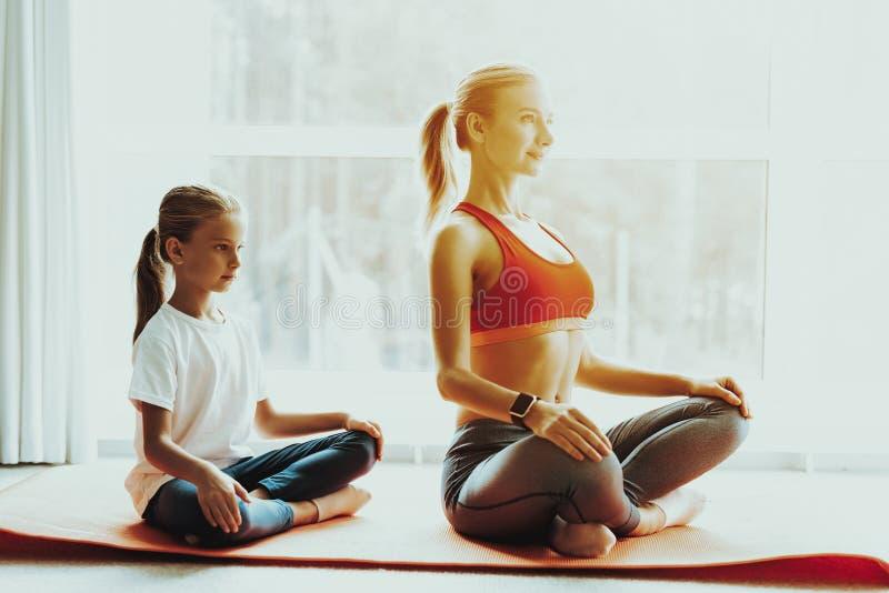 Mum en Dochteryoga Opleiding Lotus Position stock afbeeldingen