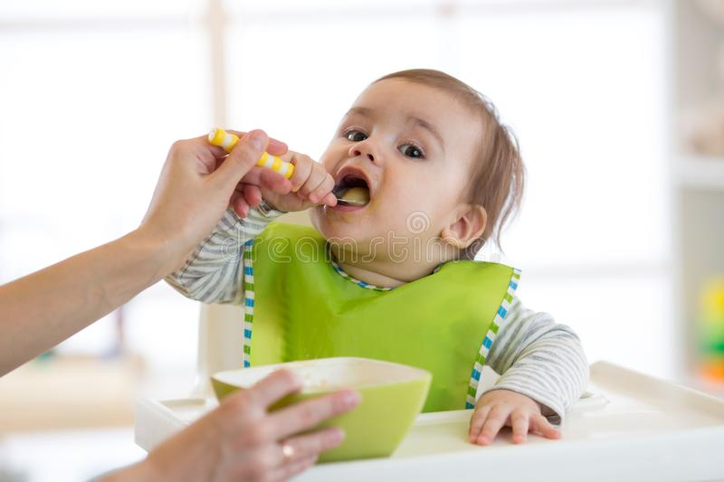 Mum feeds the little boy from a spoon with fruit puree royalty free stock images