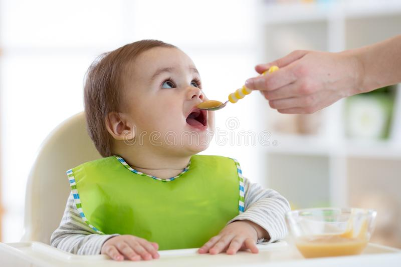 Mum feeds the little boy from a spoon with fruit puree royalty free stock photo