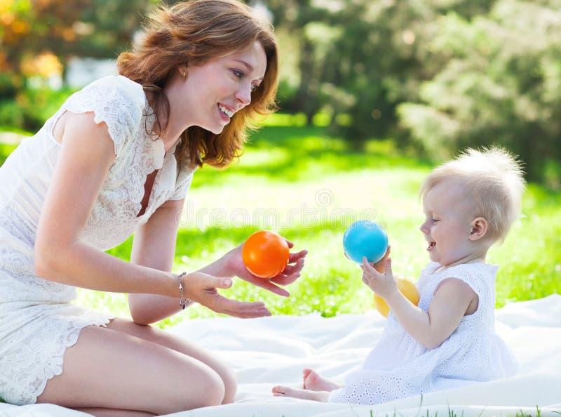 Mum feliz e sua criança que jogam no parque junto fotos de stock royalty free