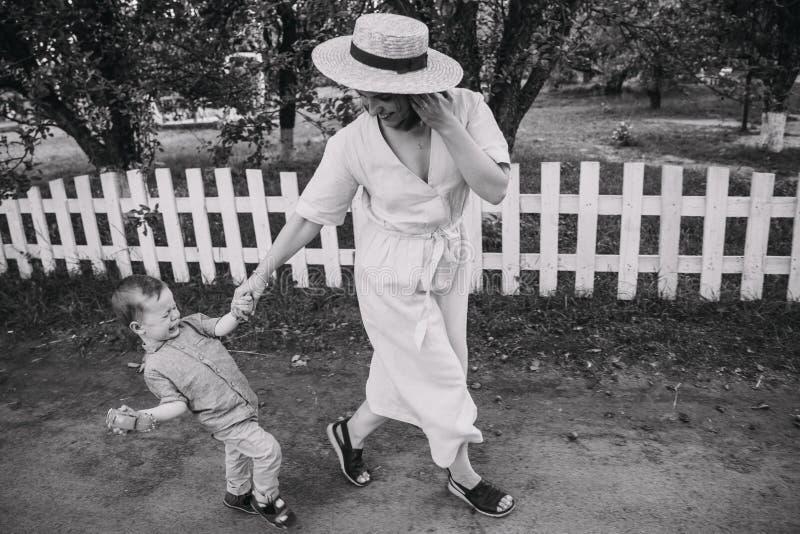 Mum gaat met het kind in het park De baby schreeuwt en breekt met a van de hand van het mamma uit stock afbeelding