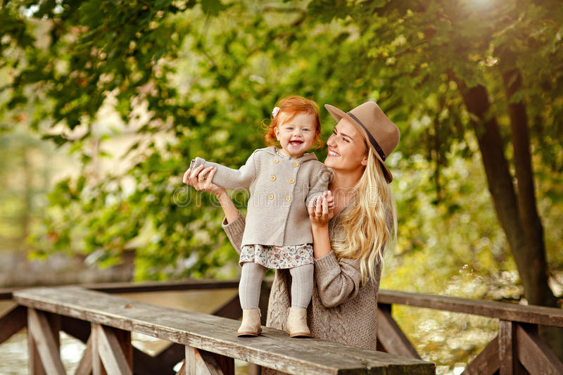 Mum gently embraces the redhead baby girl and laughing in autumn royalty free stock photography