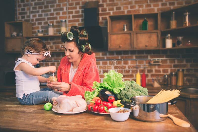 Mum hemma Barnet fostrar med det lilla barnet i det hem- köket Kvinnan som gör många uppgifter, medan sköter henne, behandla som  royaltyfria foton