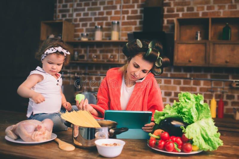 Mum hemma Barnet fostrar med det lilla barnet i det hem- köket Kvinnan som gör många uppgifter, medan sköter henne, behandla som  royaltyfri foto
