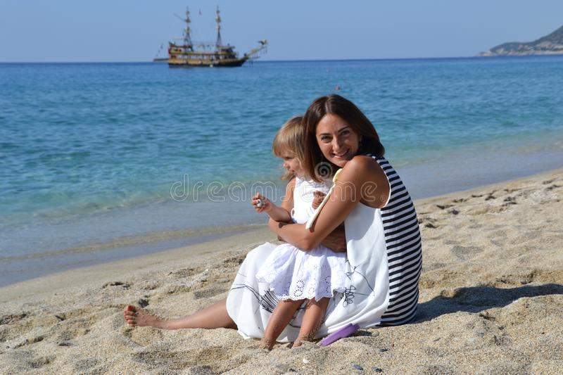 Mum and her little daughter in the hug. Mum and her little girl kid in the hug on the beach, happiness near the sea royalty free stock image