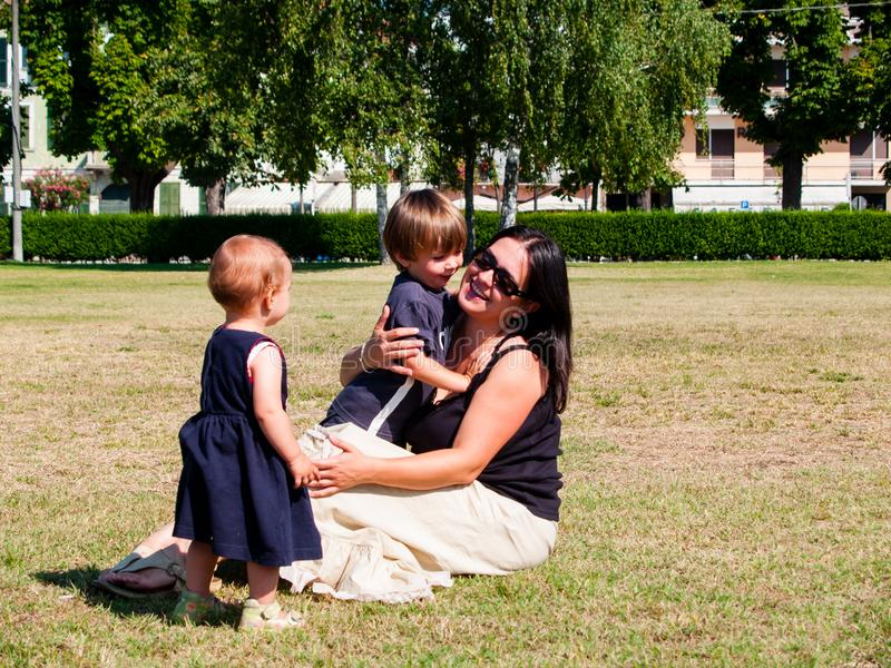 Mum with her two young children is sitting in a meadow stock photography