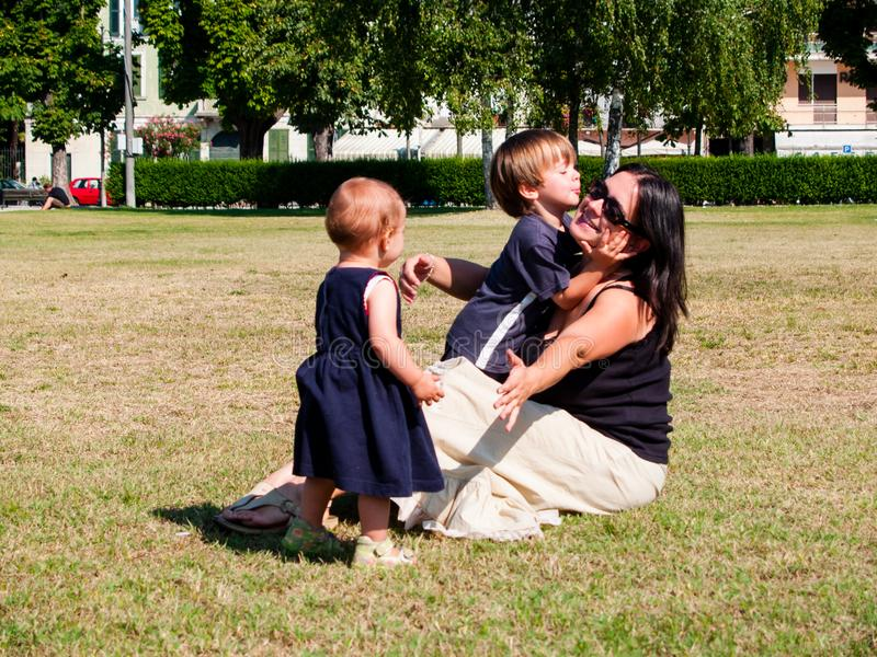 Mum with her two young children is sitting in a meadow stock photos