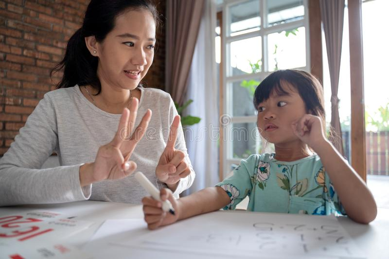 Mum and kid learning maths together at home stock image