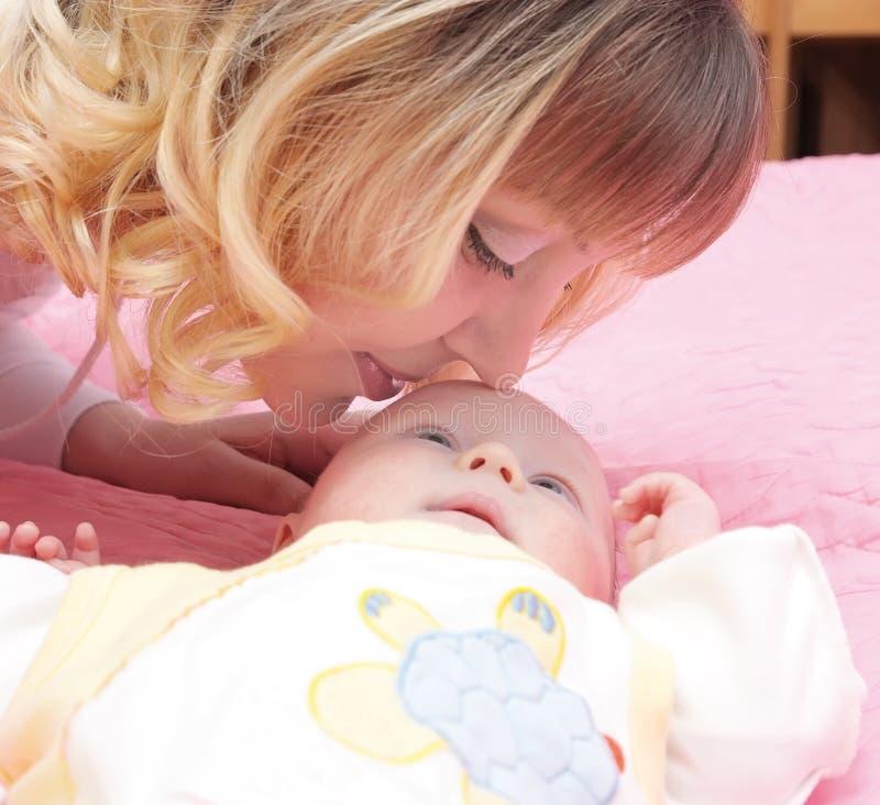 Mum kisses baby royalty free stock photography