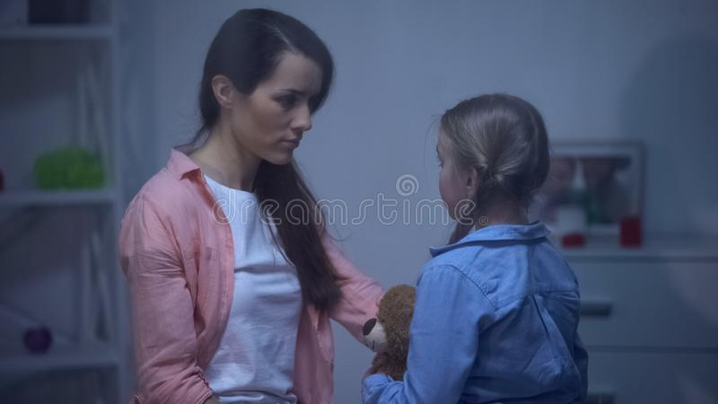 Mum looking at daughter with teddy, experiencing painful divorce, problem. Stock photo stock photo