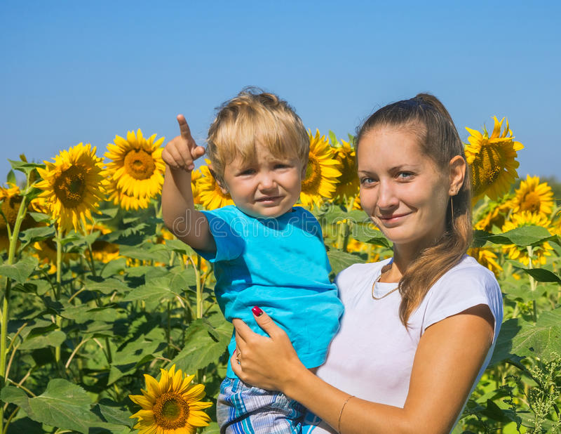 Mum met kleine zoon onder zonnebloemen royalty-vrije stock foto
