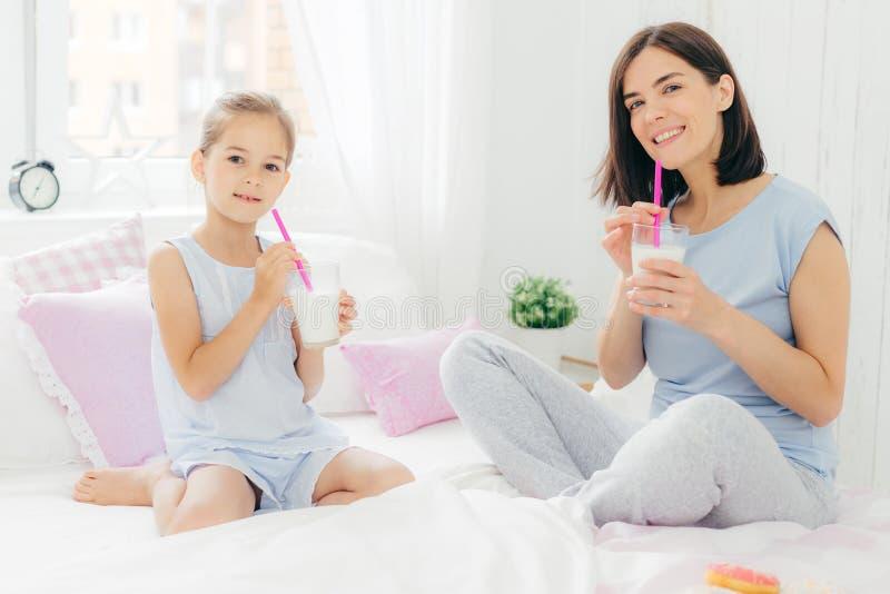 Mum novo moreno feliz e sua filha bonita para sentar-se na cama, dri imagem de stock