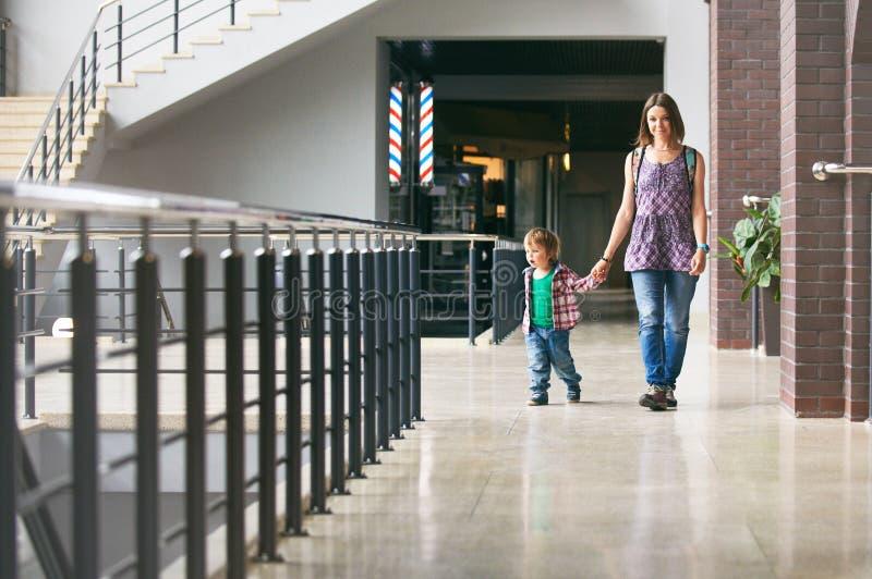 Mum och sonen som går i köpcentret arkivbild