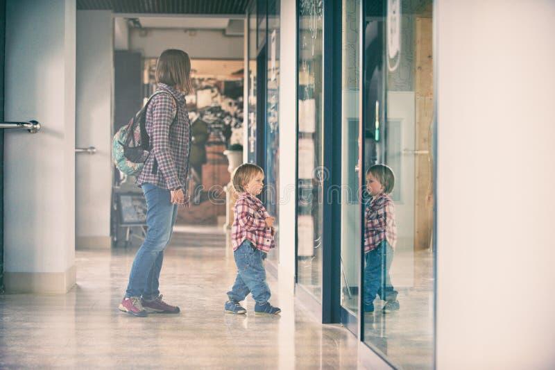 Mum och sonen som går i köpcentret royaltyfri bild