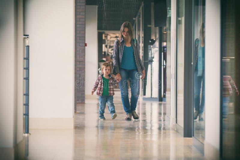 Mum och sonen som går i köpcentret arkivbilder