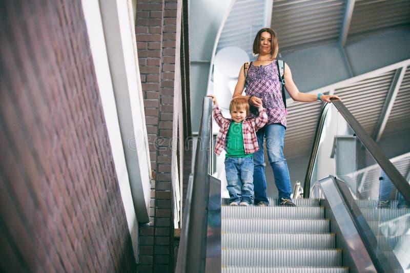 Mum och sonen som går på en rulltrappa i köpcentret royaltyfria bilder