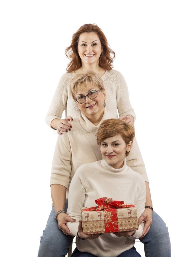 Mum op leeftijd met volwassen en dochters die glimlachen koesteren stock foto's