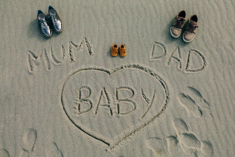 Mum, papa en baby op het zand van het strand wordt geschreven dat stock fotografie
