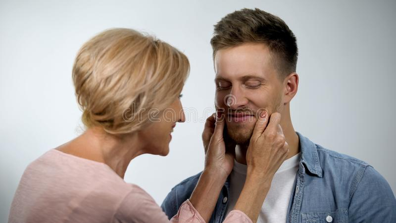 Mum pinching adult son cheeks, male smiling, overprotection effect concept royalty free stock photos