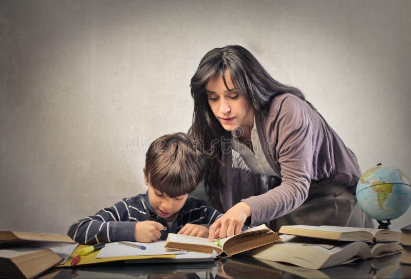 Mum pomaga jego syna z pracą domową zdjęcie stock