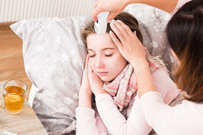 Mum som dåligt mäter dotters temperatur arkivfoton