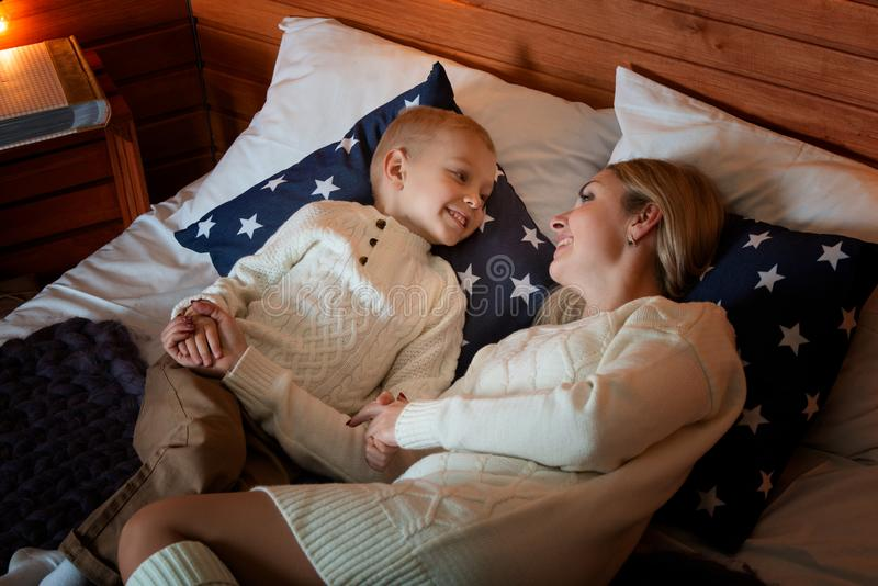 Mum with the son in winter frosty evening relax together on a bed. Family evening. stock image