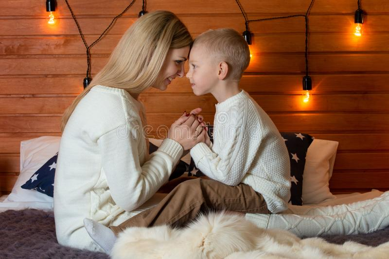 Mum with the son in winter frosty evening sit together on a bed. Family evening. stock photo
