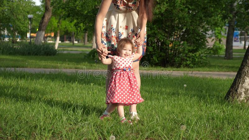 Mum walks in park on lawn with small child, mom teaches to walk little daughter, child holds the hand of his mother royalty free stock image