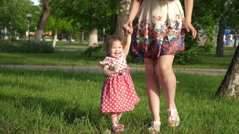 Mum walks in park on lawn with small child, mom teaches to walk little daughter, child holds the hand of his mother stock photography