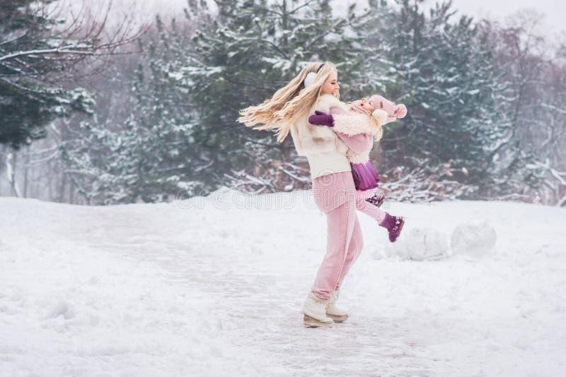 Mum wiruje jej córki w jej rękach w parku fotografia stock