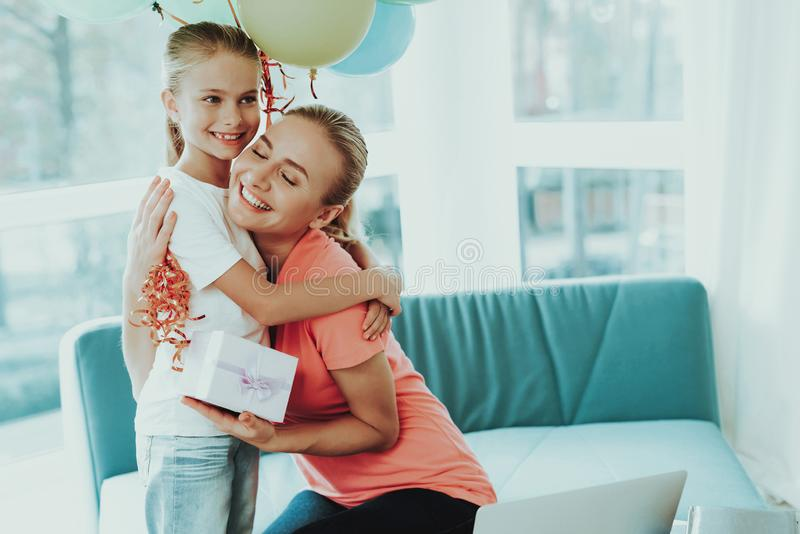 Mum Works On Laptop. Daughter`s Present Concept. Mother Works On A Laptop. Daughter`s Present Concept. Work From Home. Family Relationship. Active Holiday stock image