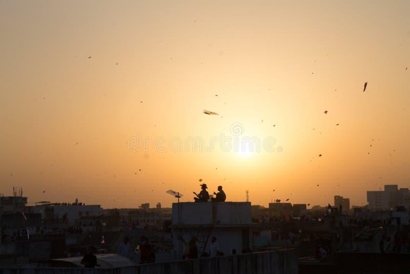 Mumbai, Índia - 8 de janeiro de 2017: os povos recolhem acima dos telhados no por do sol para comemorar o festival hindu tradicio imagens de stock royalty free