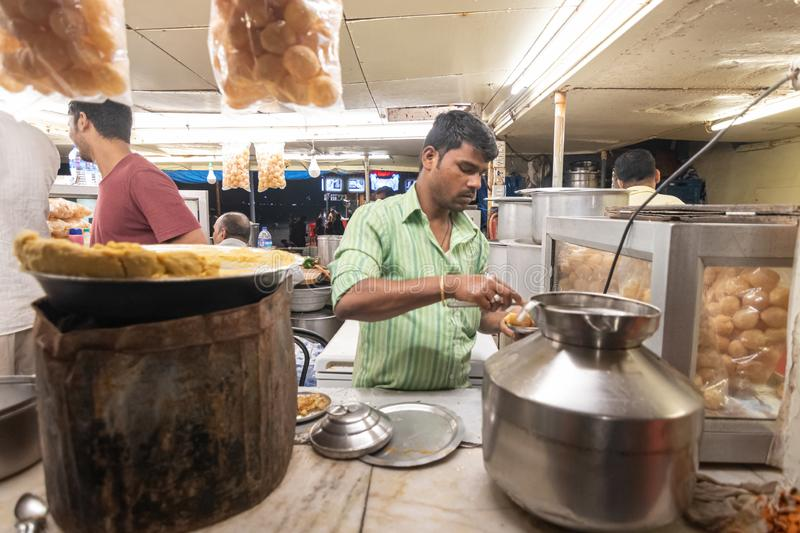 Mumbai,India,August-14-2019:Indian street food chaat and pani puri vendor preparing food. Selling street food in Mumbai is lively stock image