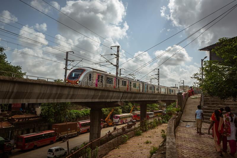 Mumbai,India,August-22-2019:Mumbai`s Reliance metro rail line running through suburban slum area of Asalpha. It has reduced. Mumbai`s Reliance metro rail line royalty free stock images