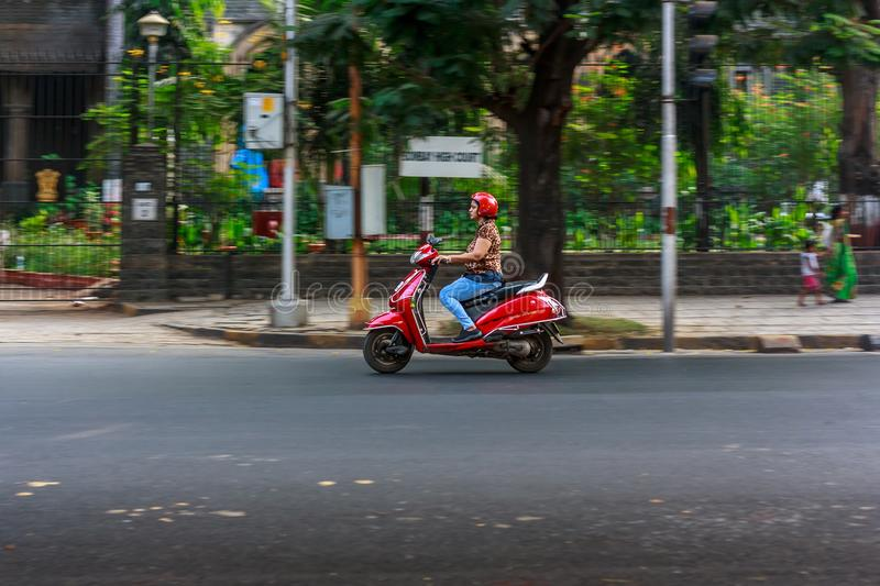 A motor bike on streets of Mumbai. MUMBAI, INDIA - DECEMBER 4, 2016 : A women riding a motor bike on streets of Mumbai royalty free stock image