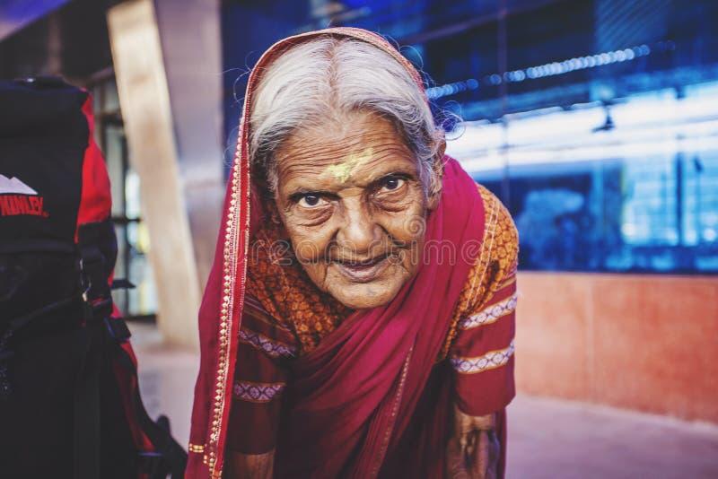 Mumbai in India: Donna indiana anziana che elemosina nella stazione ferroviaria di Mumbai fotografie stock libere da diritti